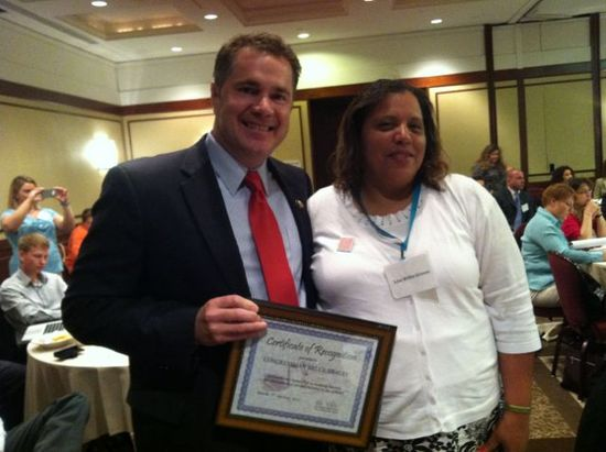 Rep. Bruce Braley, with an attendee, holding an award from SWAN for his work