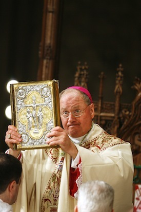 Archbishop Timothy Dolan holds a bible aloft during his first service during the Mass of Installation at St. Patrick's Cathedral