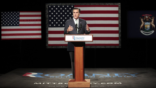 Mitt Romney stands in front of two flags in Michigan