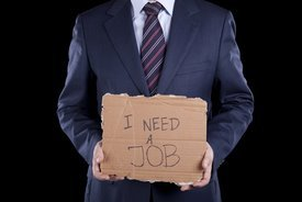 man in suit holding sign saying need job