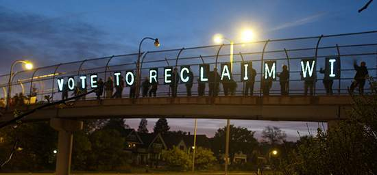lit signs on overpass saying vote to reclaim WI
