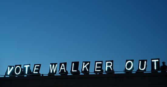lit signs on overpass saying vote Walker out