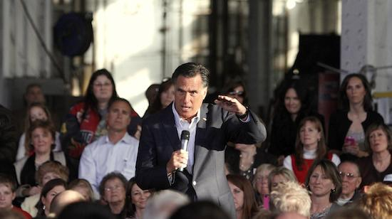 Mitt Romney at campaign event, surrounded on stage by women