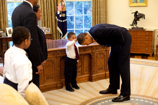 little African-American boy touching Obama's hair