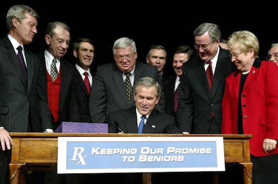 President George W. Bush signs the Medicare Modernization Act with Congress people watching.